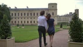 A young couple walks in the park. A young couple of lovers walk along the path in the park. They are holding hands, laughing look at each other. Happy life stock video footage