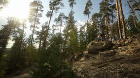 A young couple walks in a pine forest on stone rocks on a bright Sunny day. A young couple walks in a pine forest on stone rocks on a bright Sunny day stock footage