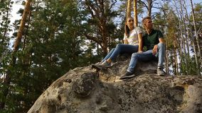 A young couple walks in a pine forest on stone rocks on a bright Sunny day. A young couple walks in a pine forest on stone rocks on a bright Sunny day stock video
