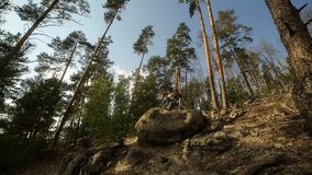A young couple walks in a pine forest on stone rocks on a bright Sunny day. A young couple walks in a pine forest on stone rocks on a bright Sunny day stock video footage