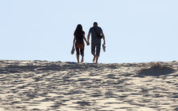 Young couple walks on sand dune. Fingal Bay. Port Stephens. Aust Stock Images