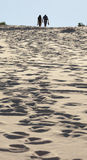 Young couple walks on sand dune. Fingal Bay. Port Stephens. Australia. royalty free stock images
