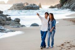 Young couple wandering along seashore. Royalty Free Stock Image