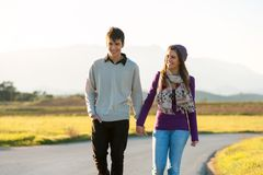 Young couple wandering in sunny countryside. Young couple wandering along road in countryside Royalty Free Stock Photo