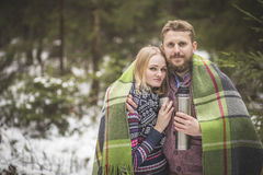 Young couple in a warm blanket with thermos flask Royalty Free Stock Image