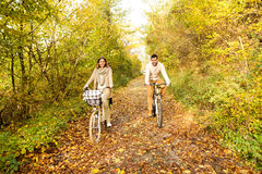 Young couple in warm clothes cycling in autumn park. royalty free stock image