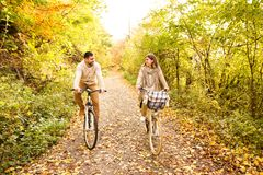 Young couple in warm clothes cycling in autumn park. Beautiful young couple in warm clothes cycling outside in autumn nature royalty free stock photo
