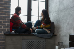 Young couple in warm knitted sweaters looking out the window while sitting on the windowsill royalty free stock images