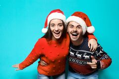 Young couple in warm sweaters and Christmas hats. On color background royalty free stock image