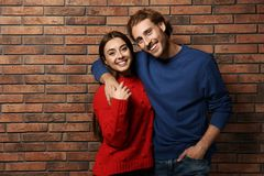 Young couple in warm sweaters. Near brick wall stock photography