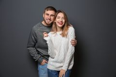 Young couple in warm sweaters. On dark background stock photography