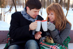 Young couple warming themselves in the winter park. Young beloved couple warming themselves in the winter park Royalty Free Stock Photography