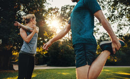 Young couple warming up for morning workout in the park Stock Images