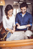 Young couple washing dishes in the kitchen Royalty Free Stock Images