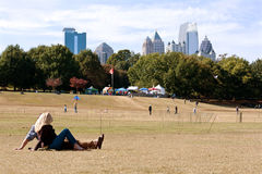 Young Couple Watches Kites Being Flown In Autumn Festival. Atlanta, GA, USA - October 26, 2013: A young couple lays on the grass and watches people fly kites at royalty free stock images