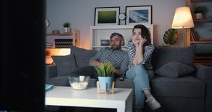 Young couple watching boring film on TV at home at night yawning relaxing. Young couple man and woman watching boring film on TV at home at night yawning stock video footage