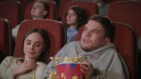 Young couple watching horror film in movie theatre. Guy sprinkle popcorn