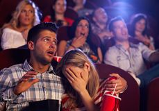 Young couple watching horror in movie theater. Young couple watching horror movie in cinema, girl turning her head away with fear stock photo