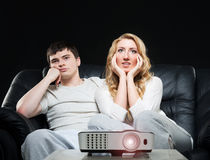 Young couple watching a movie while sitting on a sofa Royalty Free Stock Photo