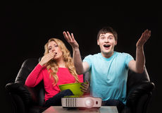 Young couple watching a movie while sitting on a sofa Stock Image