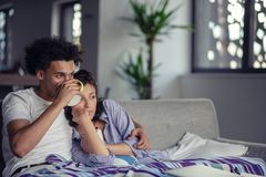 Young couple watching a movie on their laptop in bed royalty free stock images