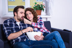Young couple watching movie on tv and eating popcorn in living r Stock Image