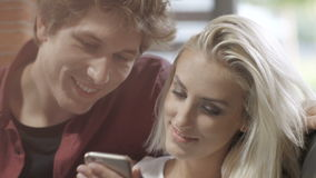 Young couple watching photos on mobile phone in modern loft interior. stock footage