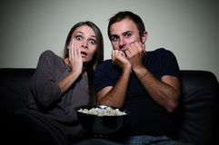Young couple watching scary movie on tv Royalty Free Stock Photo