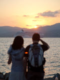 Young couple watching sunset. Over the bay of Saint-Tropez. Cruise ship in the background Royalty Free Stock Photo