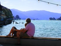 Young Couple Watching Sunset. A young couple relaxing on the pier, watching the sunset Royalty Free Stock Photos