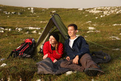 Young couple watching the sunset while camping in the mountains Stock Image