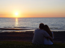 Young couple watching the sunset. Young couple of man and woman sitting on the beach watching sunset Stock Photo