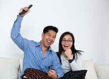 Young couple watching television at home Stock Images