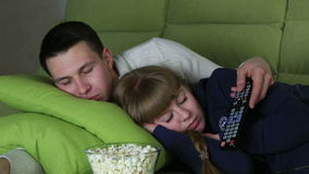 Young couple watching television with popcorn and stock video footage