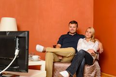 Young couple watching tv cuddling sitting armchair Royalty Free Stock Image