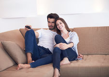 Young couple watching tv at home Stock Images