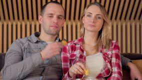 Young Couple Watching TV on the Sofa in the Living Room end eating chips stock video footage
