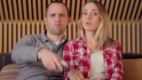 Young Couple Watching TV on the Sofa in the Living Room end eating chips stock video