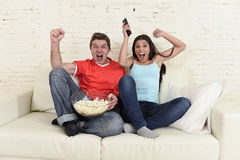 Young couple watching tv sport football game excited celebrating Royalty Free Stock Images