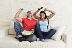 Young couple watching tv sport football game excited celebrating Stock Photos