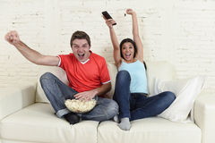 Young couple watching tv sport football game excited celebrating. Together crazy happy goal raising arms in victory gesture jumping on home sofa couch screaming Royalty Free Stock Image