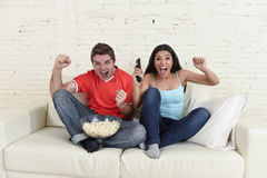 Young couple watching tv sport football game excited celebrating. Together crazy happy goal raising arms in victory gesture jumping on home sofa couch screaming Royalty Free Stock Photography