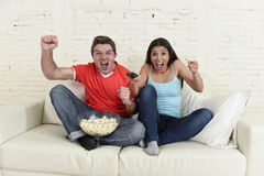 Young couple watching tv sport football game excited celebrating. Together crazy happy goal raising arms in victory gesture jumping on home sofa couch screaming Stock Photography