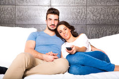 Young couple watching TV together on the Sofa Stock Image