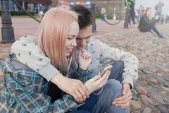 Young couple watching a video on a smartphone on the beach of the river. They smile, seeing the funny video Royalty Free Stock Images