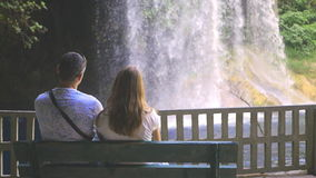 Young couple watching the waterfalls stock video footage