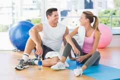 Young couple with water bottles chatting at gym Royalty Free Stock Photography