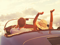 Young Couple Wathcing the Sunset in Vintage Sports Car Royalty Free Stock Photography