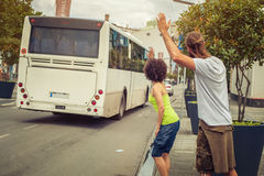 Young couple waving goodbye to their friends on the bus Stock Photo