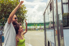 Young couple waving goodbye to their friends on the bus. At bus station Stock Image